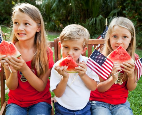 Children, ages 4, 7 and 9, eating watermelon at July 4th or Memorial Day picnic