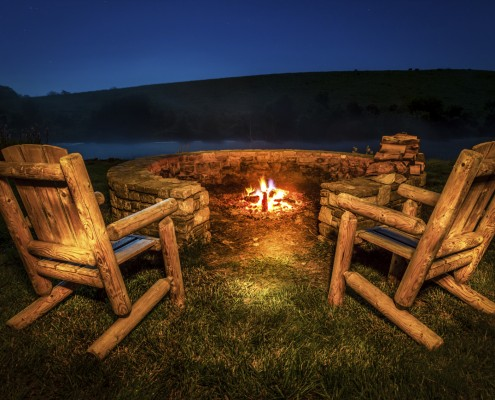 Two empty chairs by the firepit near a lake at night