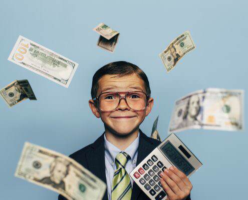 A young boy accountant wearing glasses and suit is holding a calculator while U.S. currency falls from above. He is smiling and ready to do your taxes for the IRS and make your tax refund much more money.