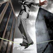 A business man balancing across a tight rope, downtown.